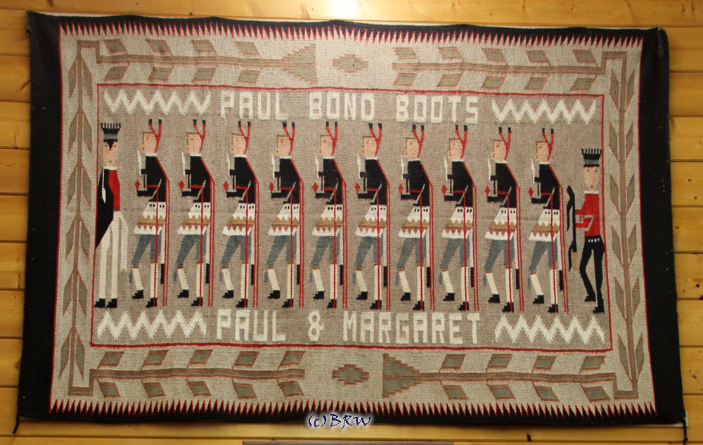 A woven rug that hangs on the wall of Paul Bond Boots